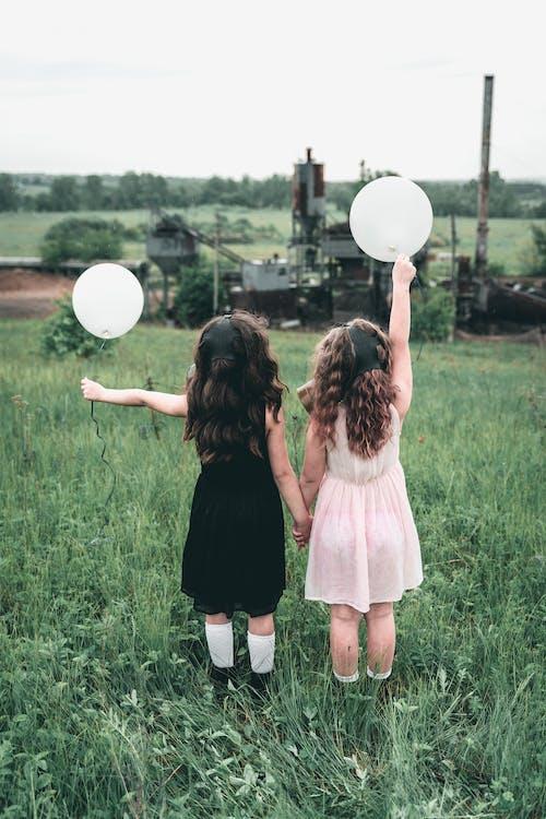 Children Standing on the Grassland Holding a Balloon
