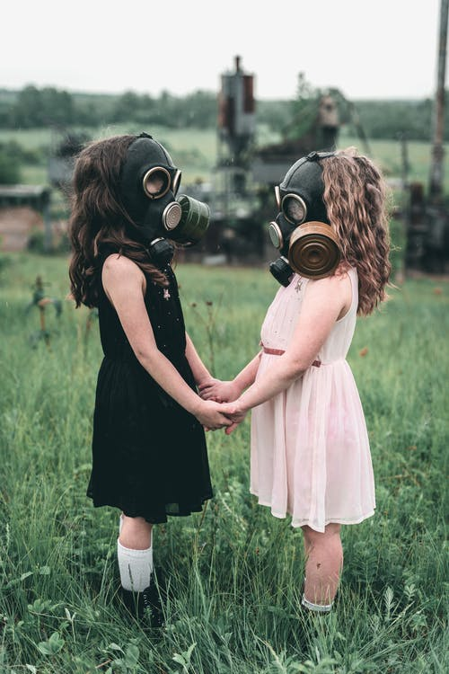 Children wearing Gas Mask holding each other's Hands