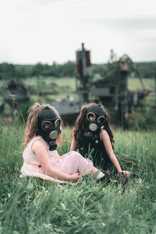 Children wearing Gas Mask Sitting Together on Grass