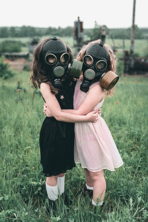 Kids in Gas Mask Hugging Each Other