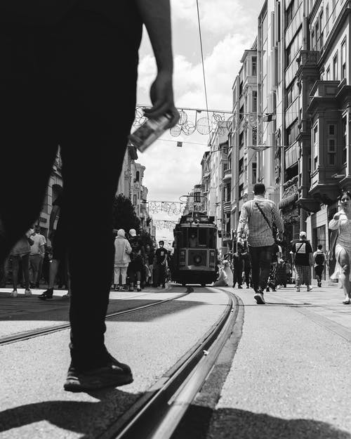 Grayscale Photo of Person in Black Pants Standing on the Tramway