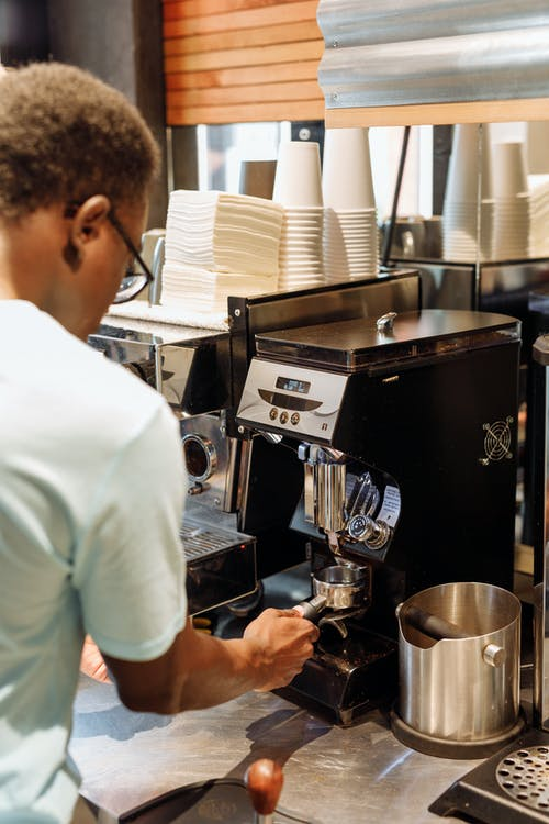 Man in White T-shirt Standing in Front of Espresso Machine