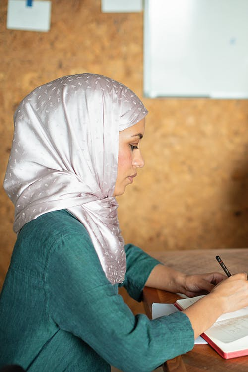 Woman in White Hijab and Green Dress Holding Black Pen