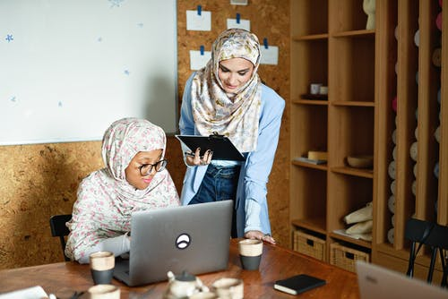 Woman in White Floral Hijab Using Silver Laptop