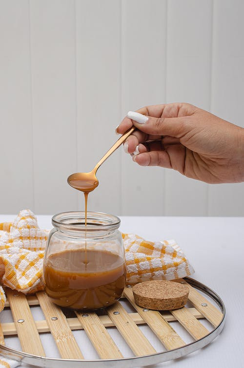 Person Holding White Plastic Spoon and Clear Glass Jar With Brown Liquid
