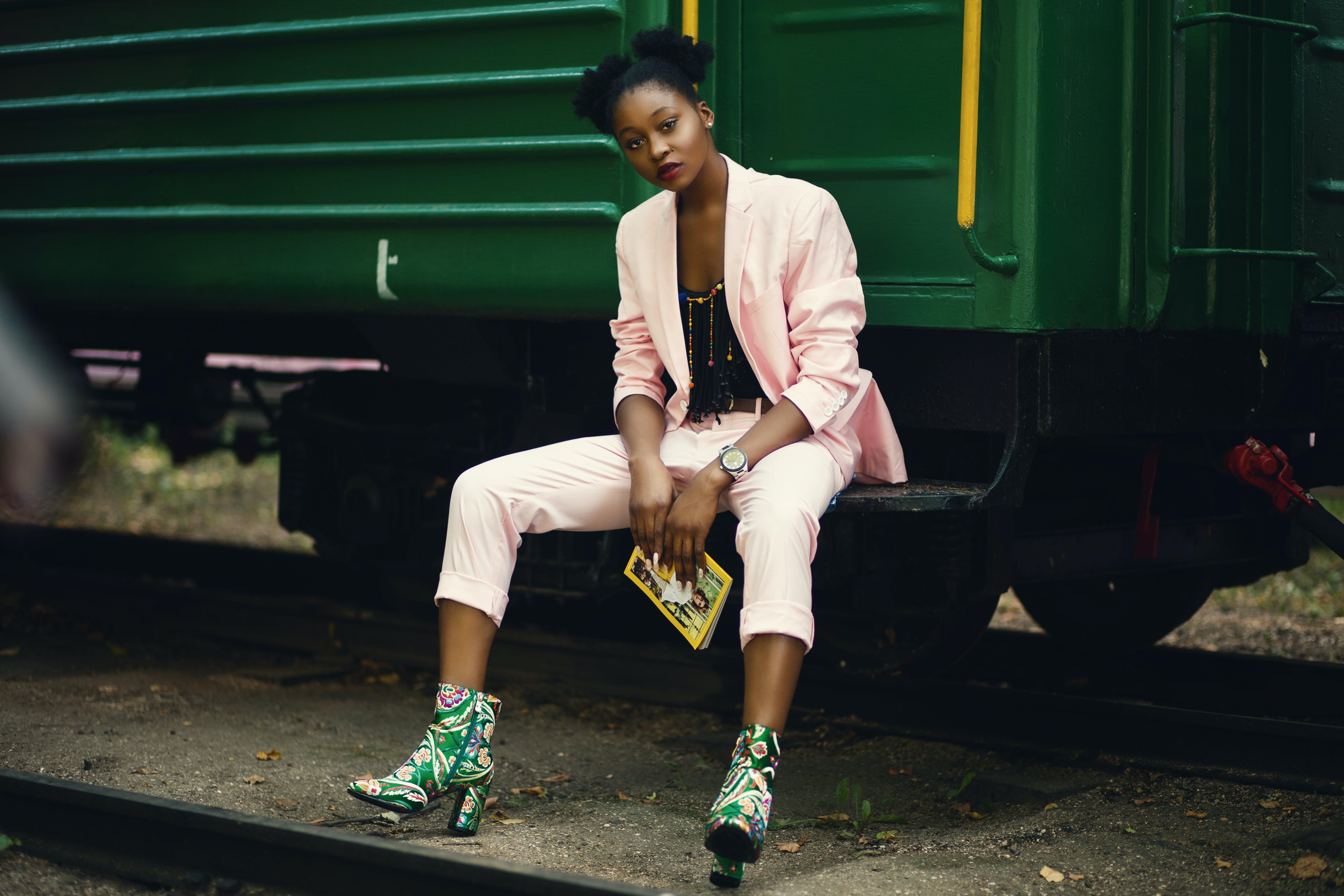 Woman in Pink Blazer Sitting on Green Train