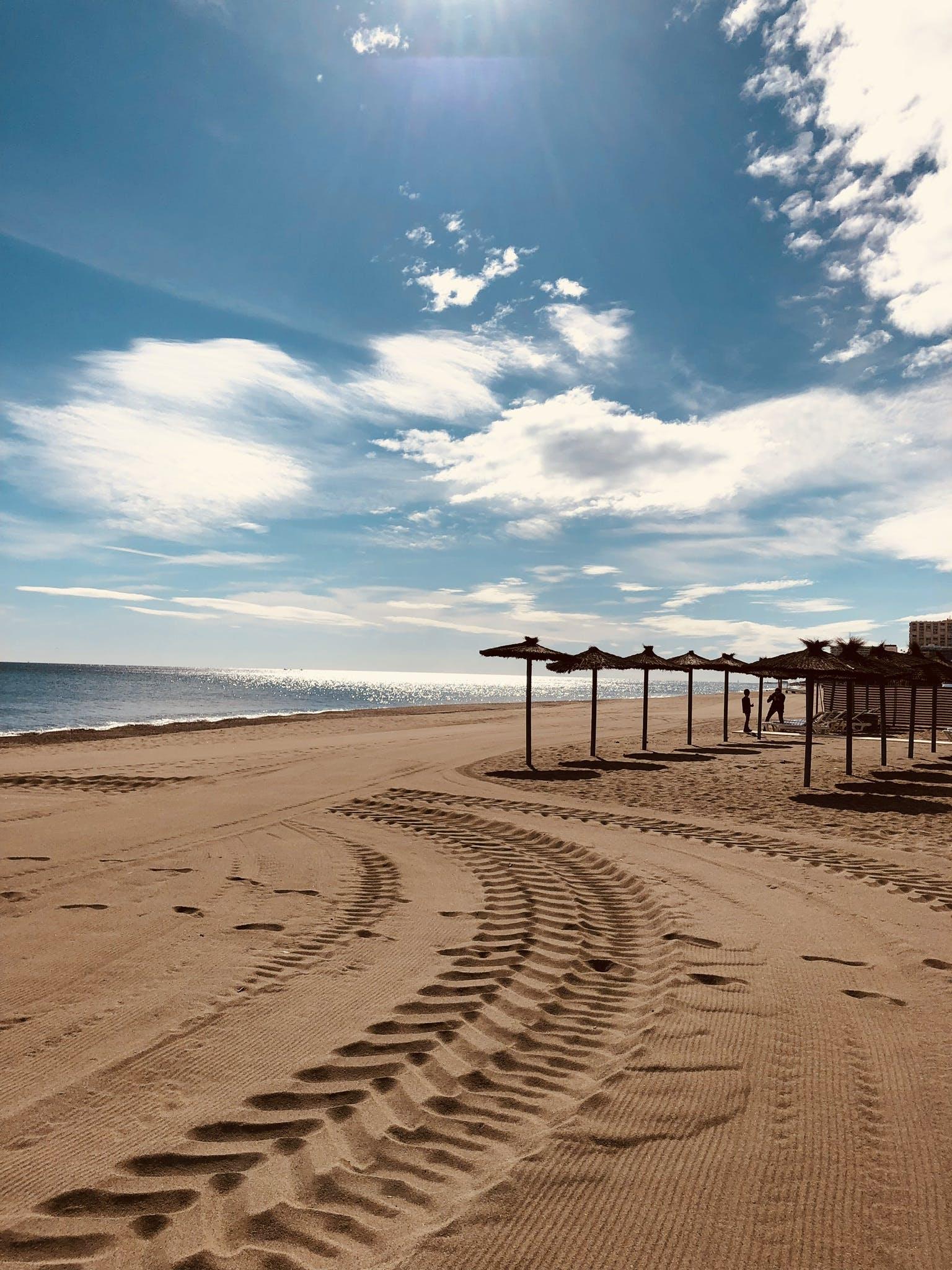 Brown Sand Near Seashore Under Cloudy Sky