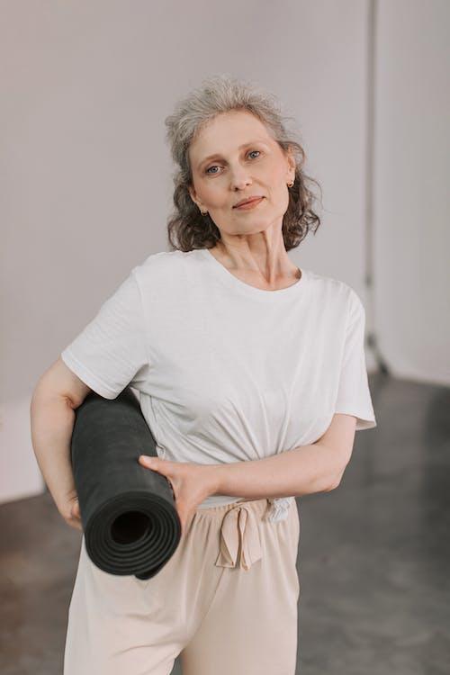 Woman in White Shirt Holding Black Yoga Mat