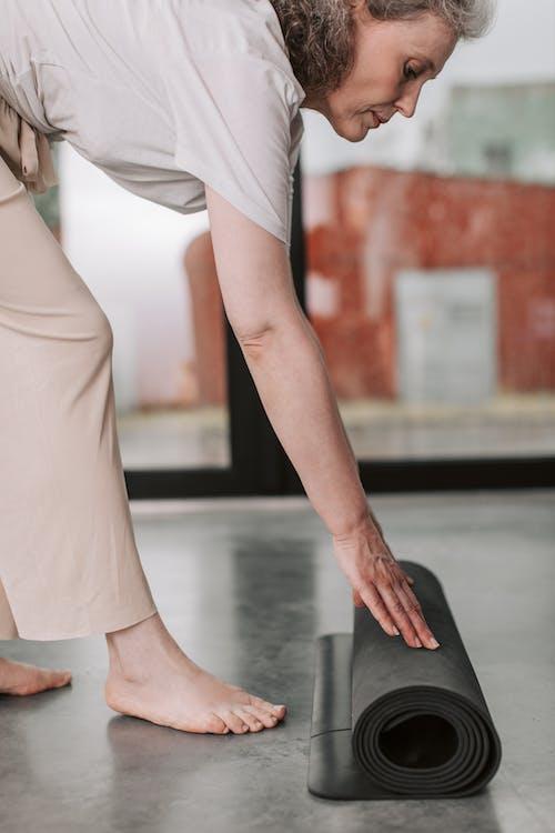 Woman in White Dress Sitting on Black Yoga Mat