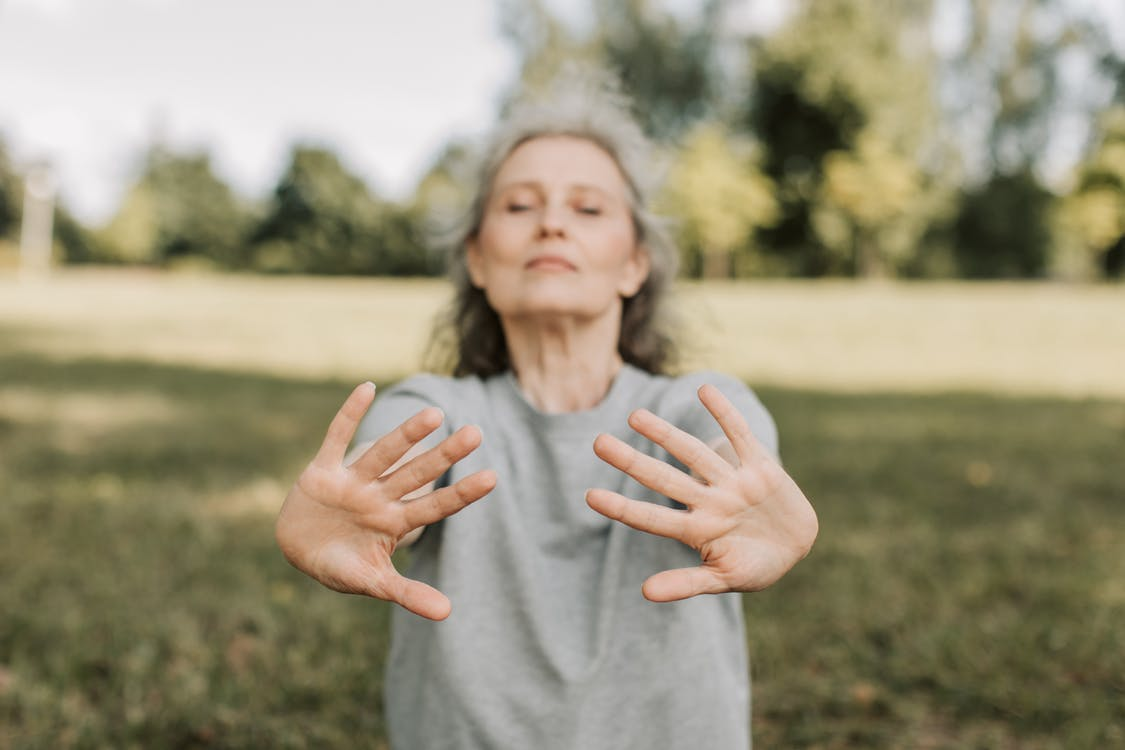 Woman deep breathing performing tai chi for stress relief and calming the nervous system
