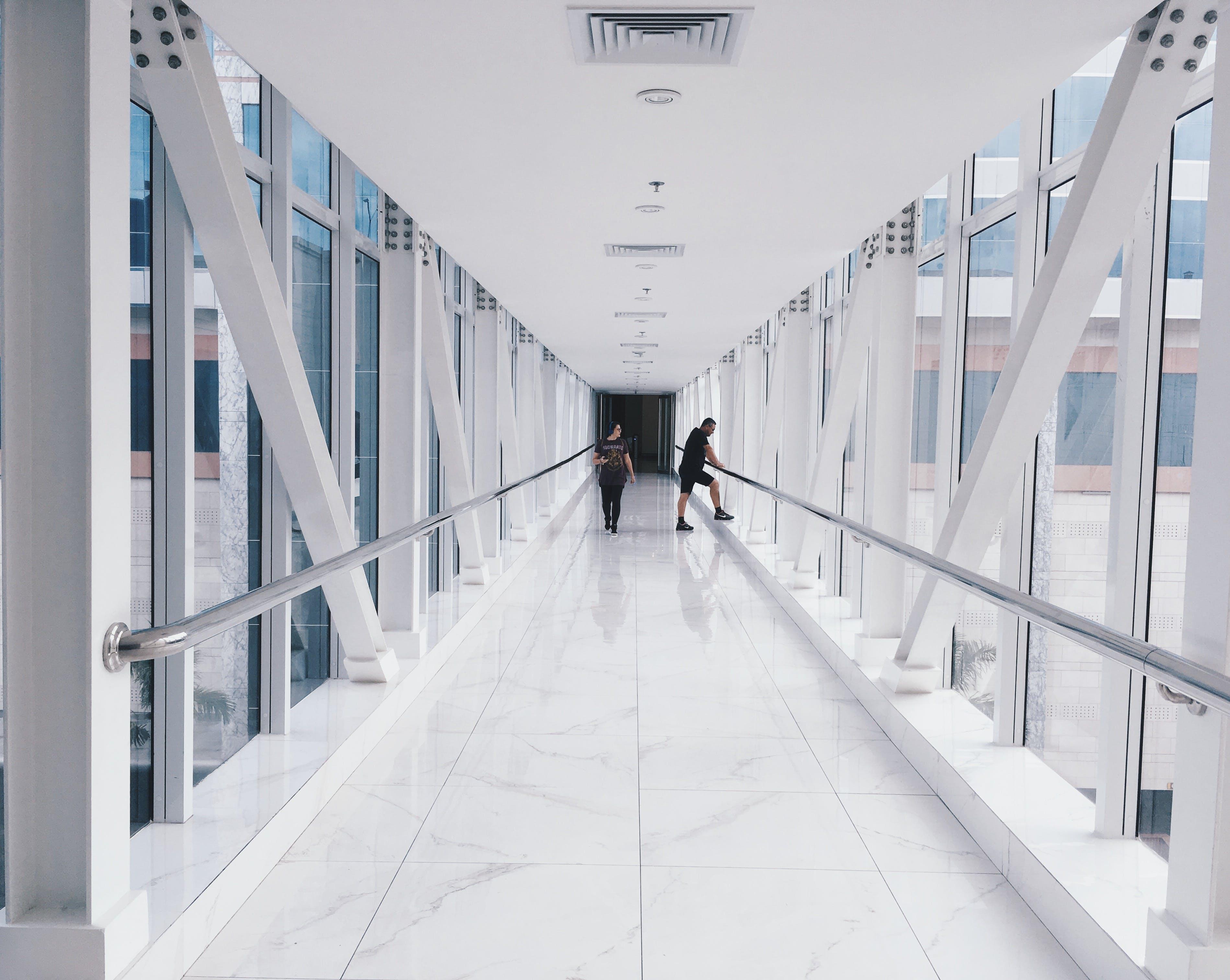 Two People Standing on Hallway Near Glass Window