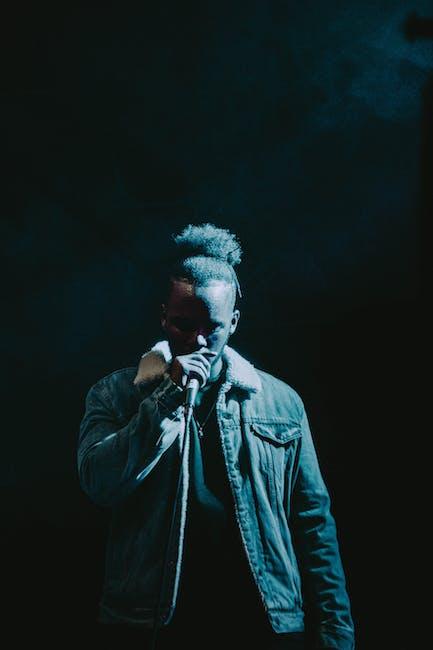 Man wearing denim jacket singing on stage