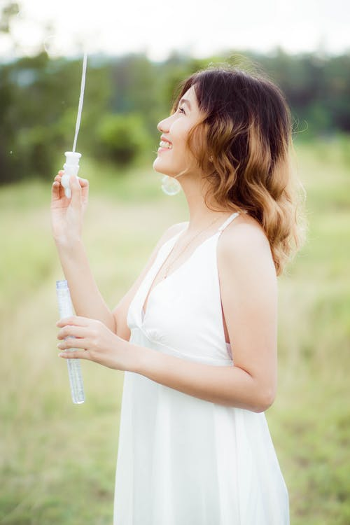Woman in White Tank Top Holding White and Blue Toothbrush