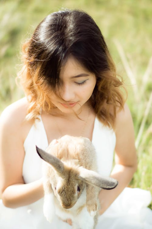 Close-Up Photo of a Woman Holding a Cute Bunny