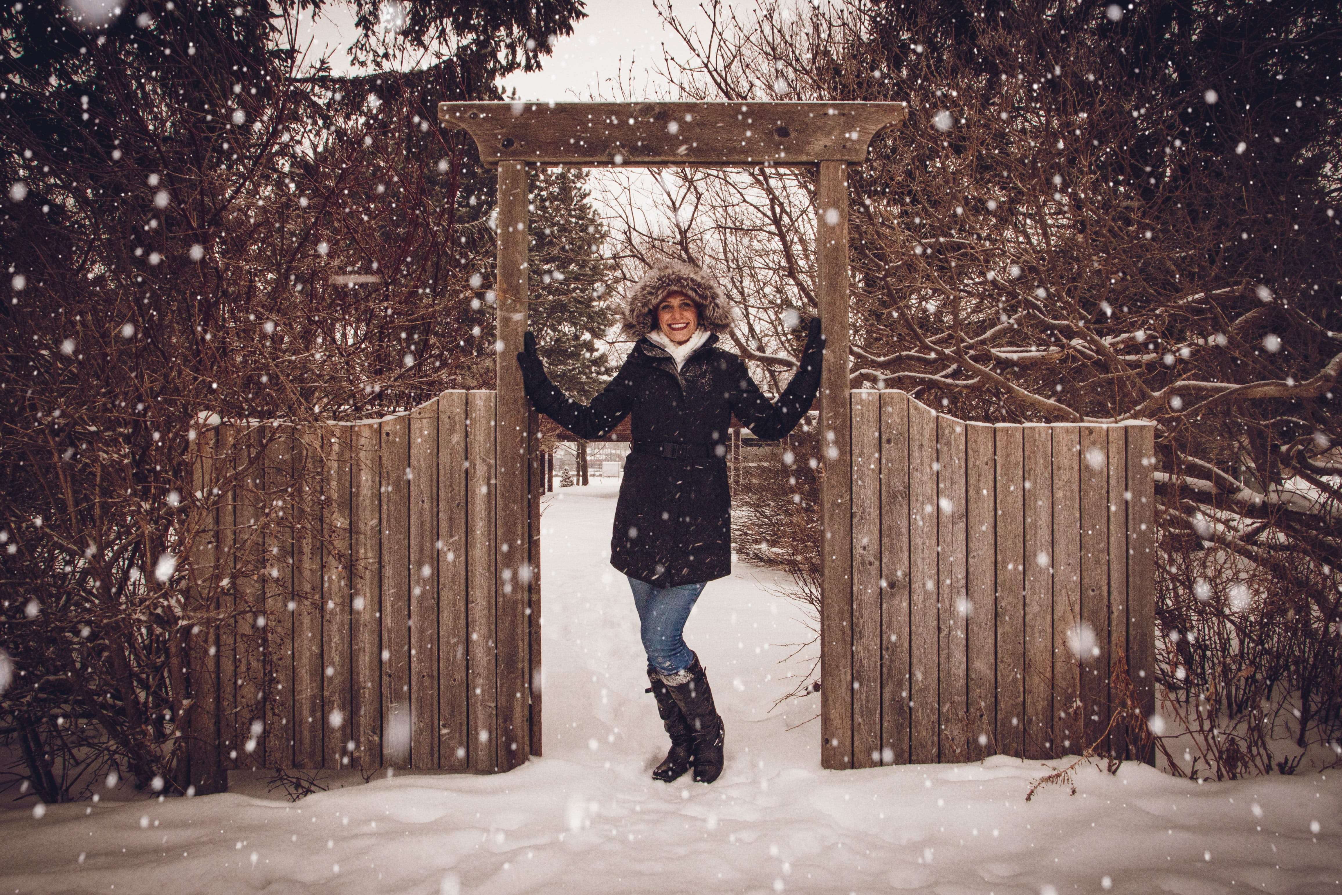 Woman in Black Coat Beside Fence during Snow