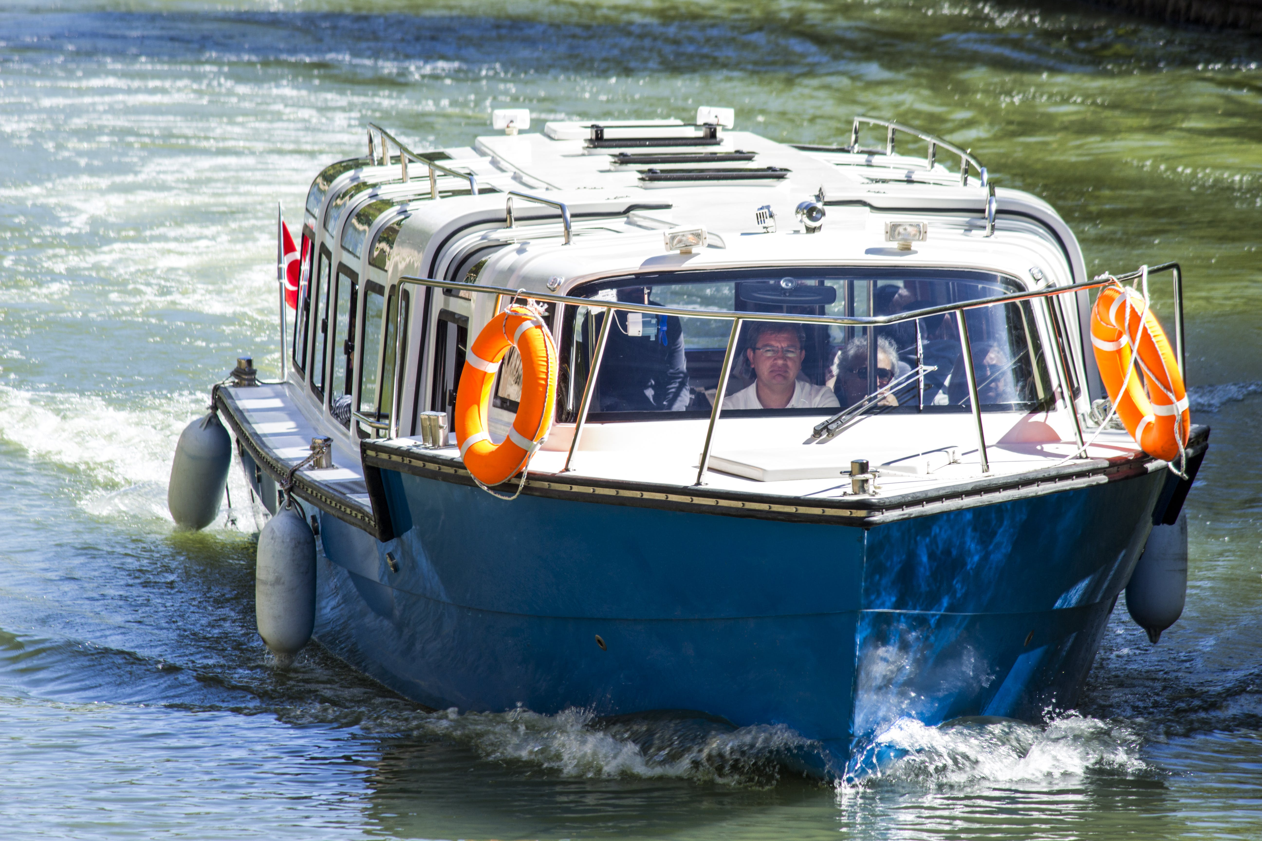 Man in White Shirt Driving Blue and White Boat