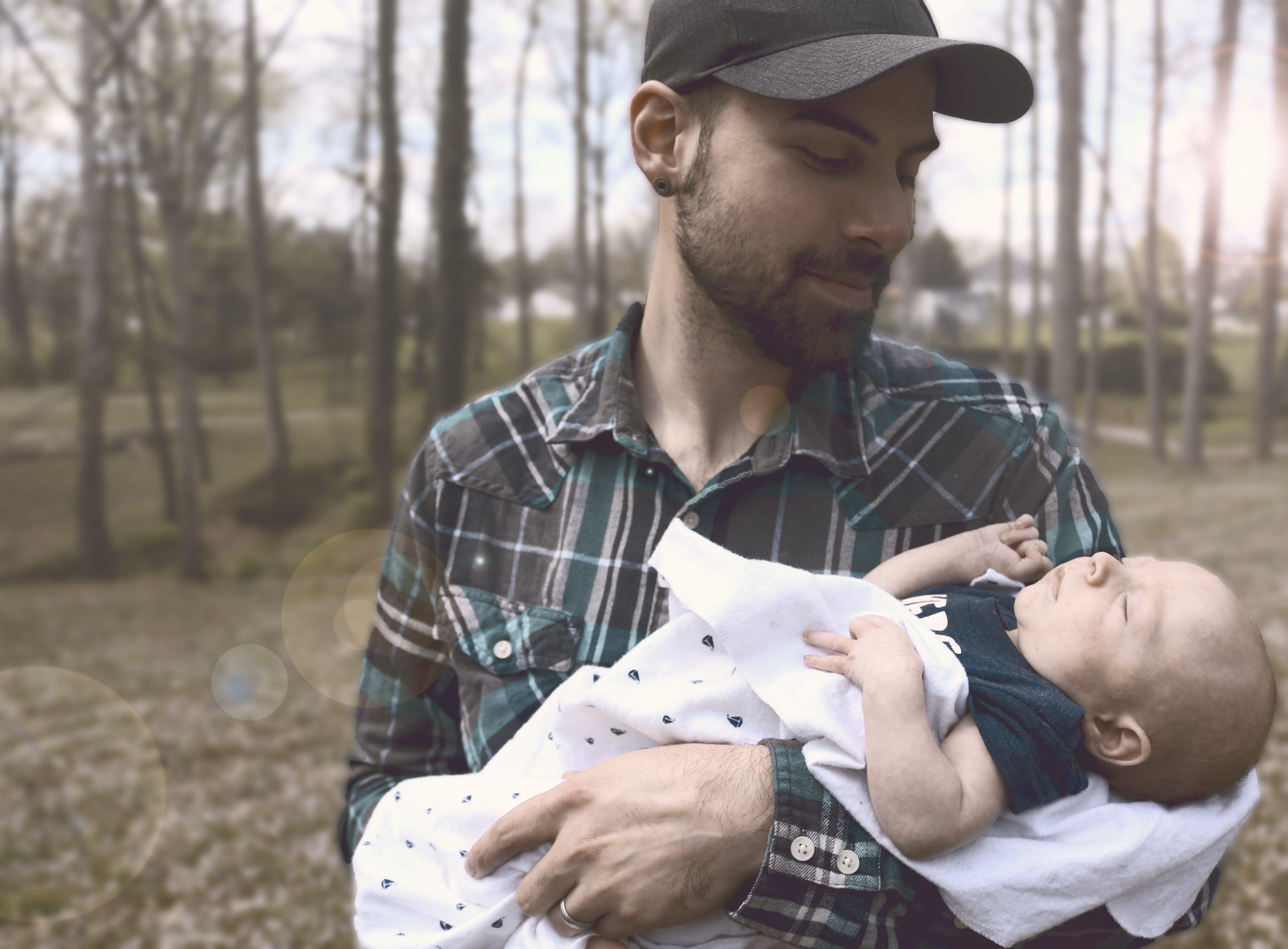 Man Holding Baby during Daytime