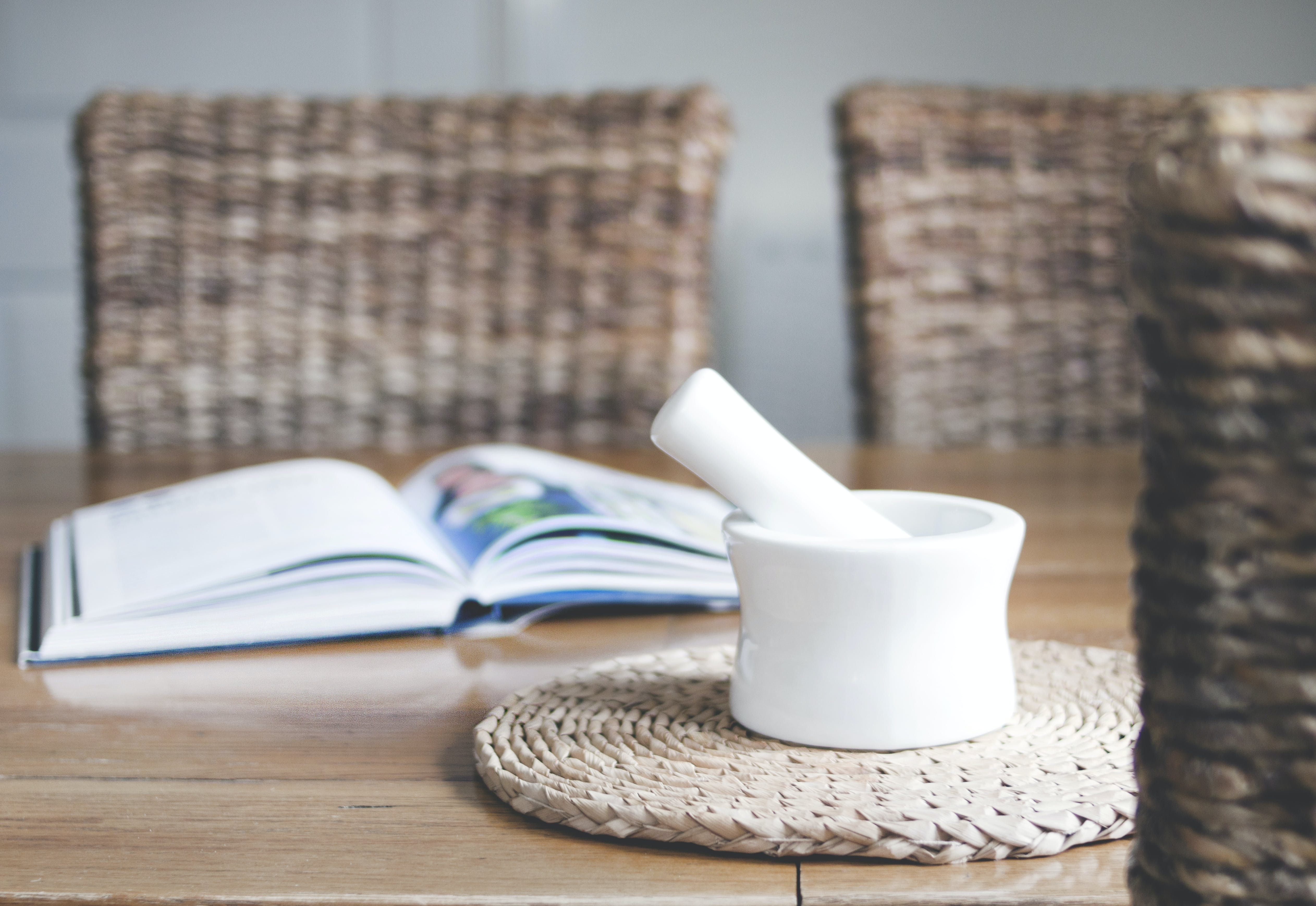White Ceramic Mortar and Pestle Beside Book
