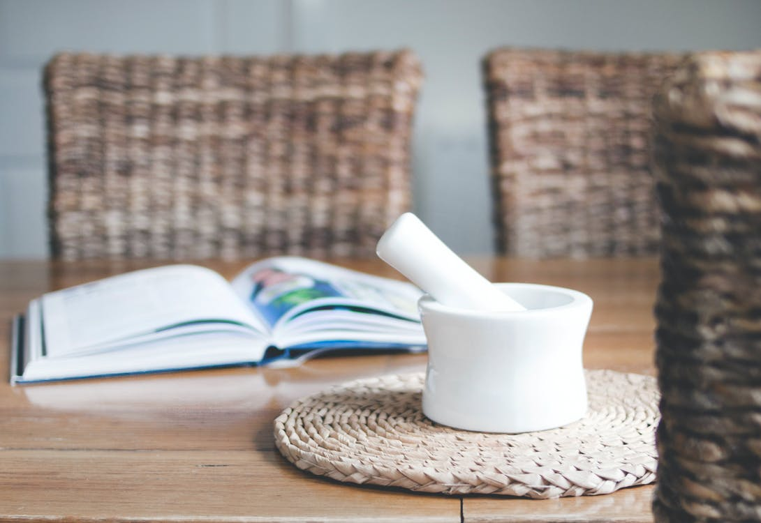 White Ceramic Mortar and Pestle Beside Book