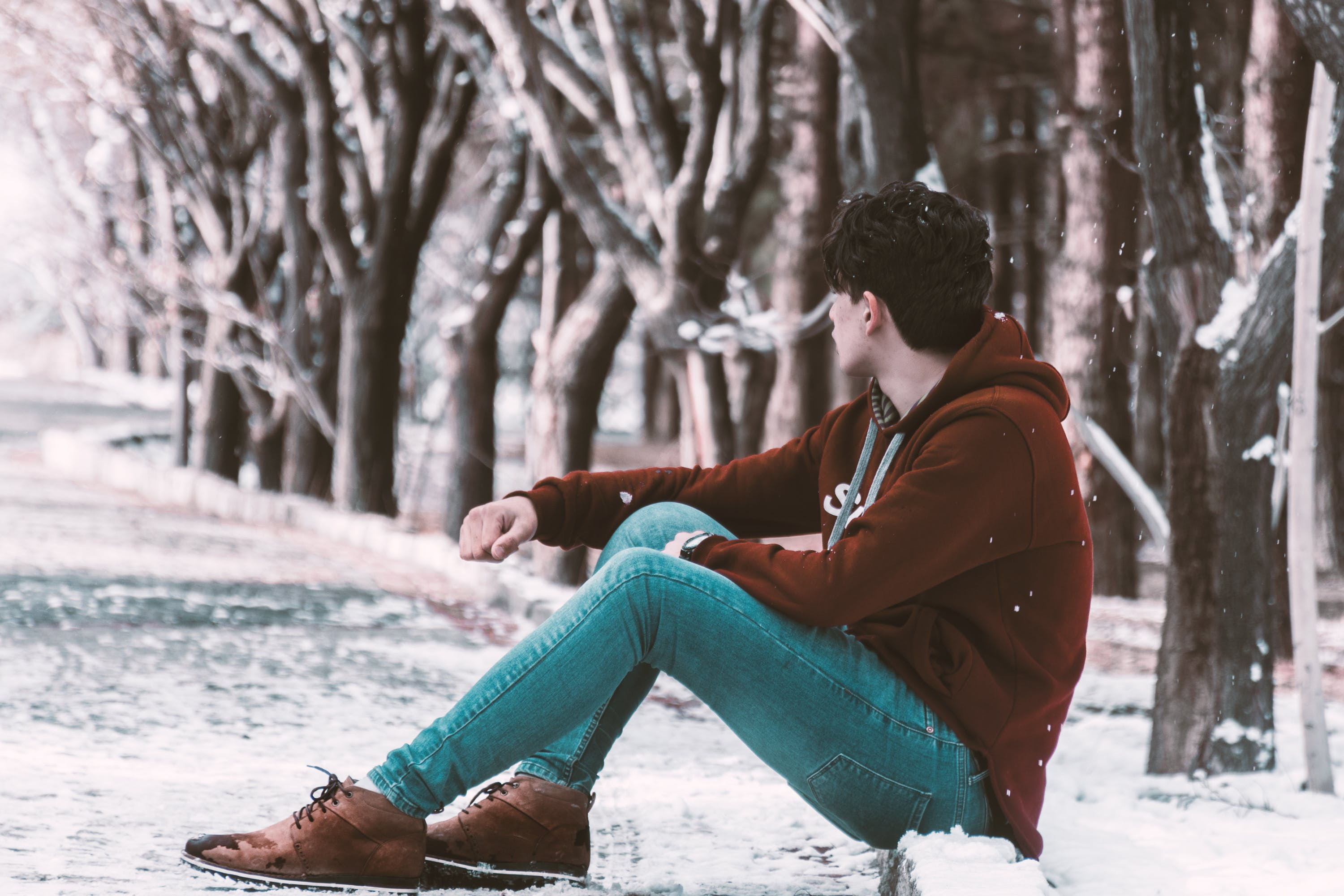 Man Sitting on Ground With Snow