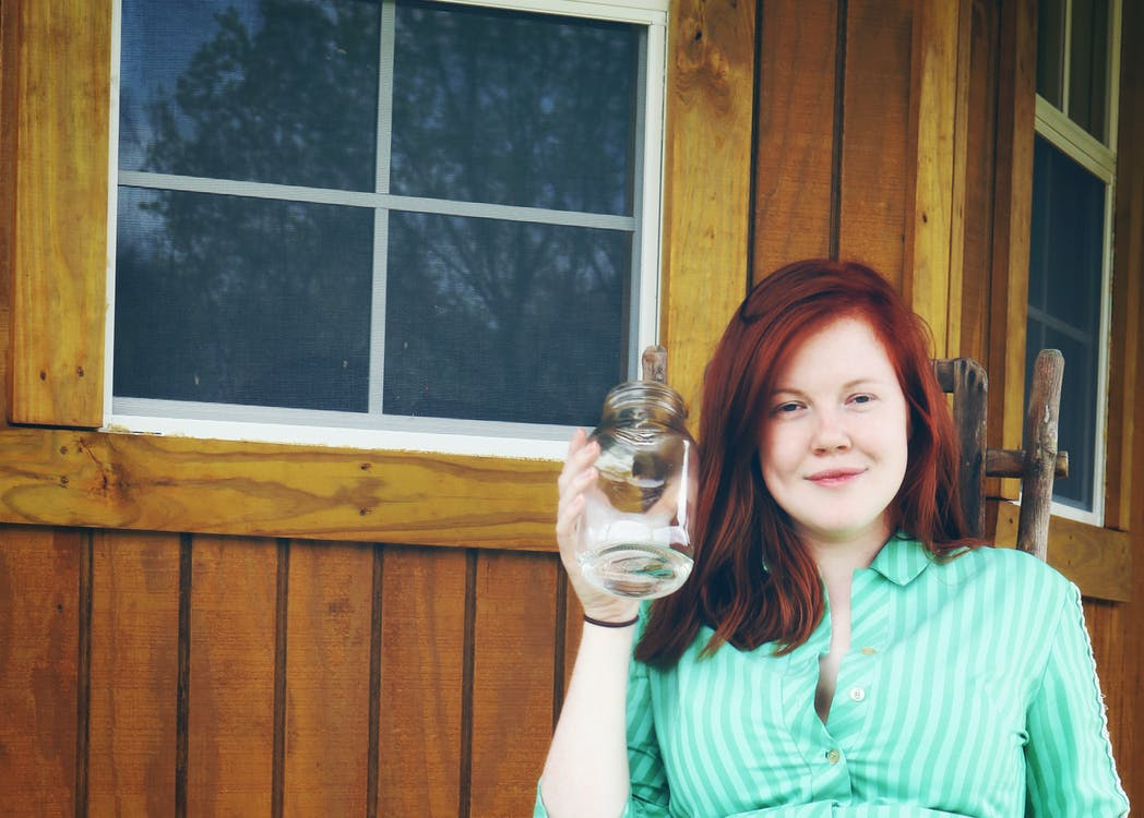 Woman in Green Button Up Collared Shirt Holding Clear Glass