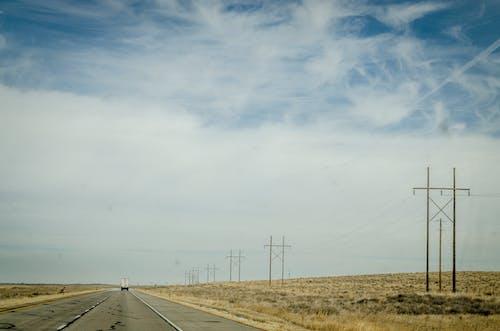 Kostnadsfri bild av asfalt, dagsljus, fält, fordon