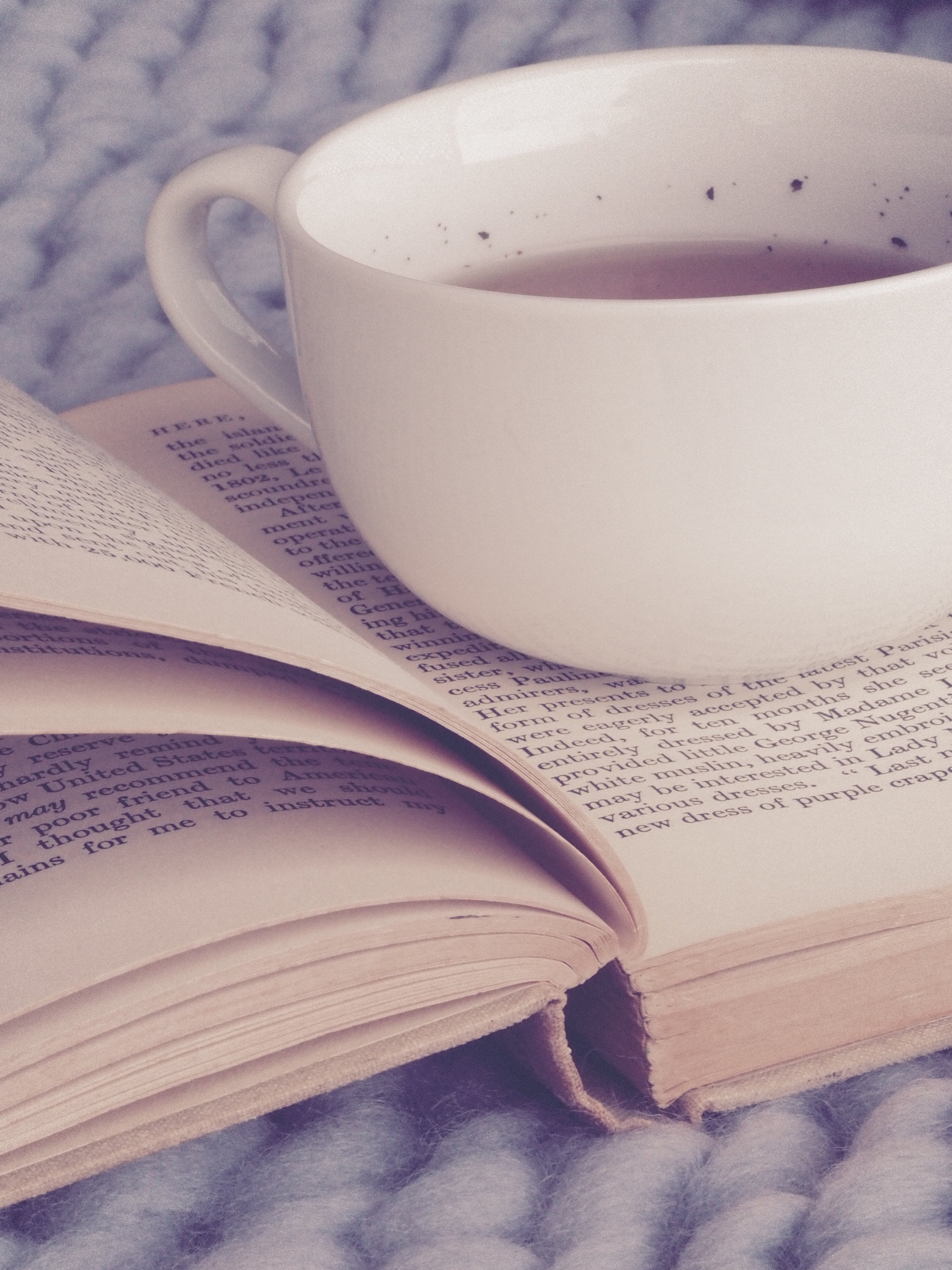 White Ceramic Cup on Top of Book