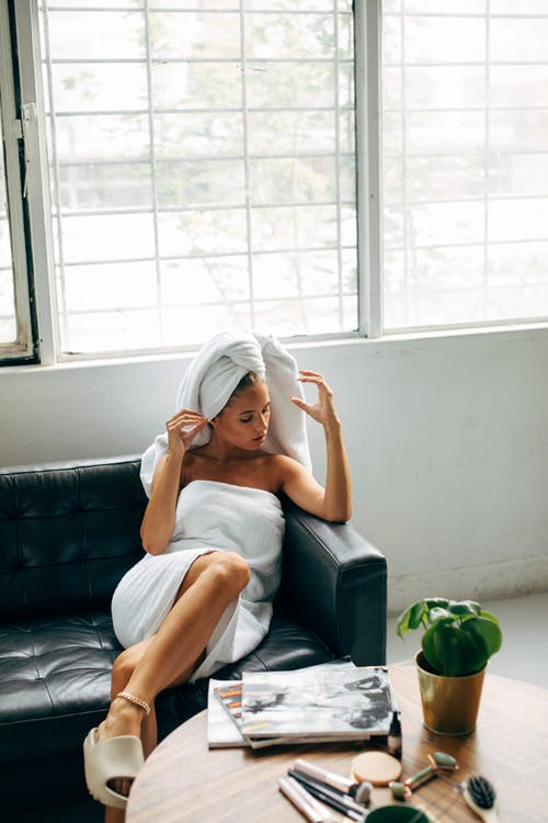 Woman in White Tank Top Sitting on Black Leather Couch