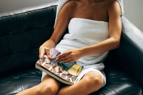 Woman in White Towel Sitting on Black Couch
