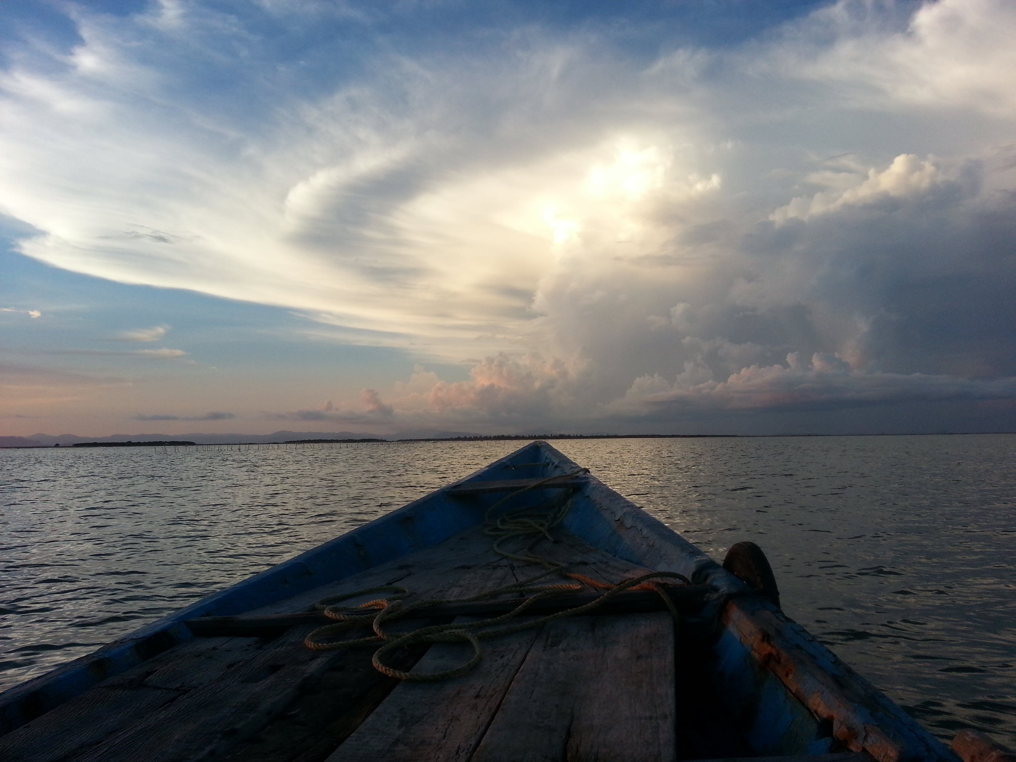 Blue Rowboat on Water Under White Clouds during Daytime