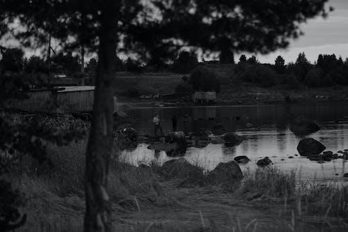 Grayscale Photo of People on Lake