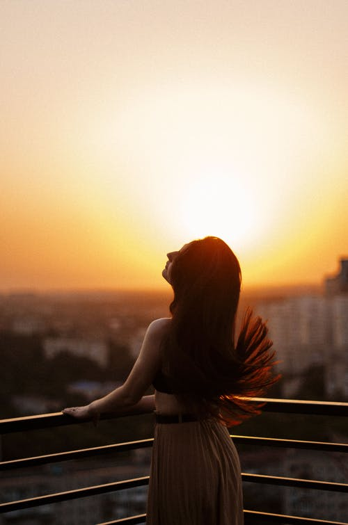 Woman in White Tank Top Standing on Balcony during Sunset