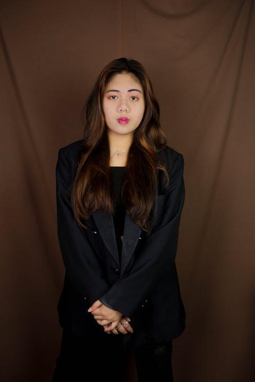 Woman in Black Blazer Standing Near Brown Wall