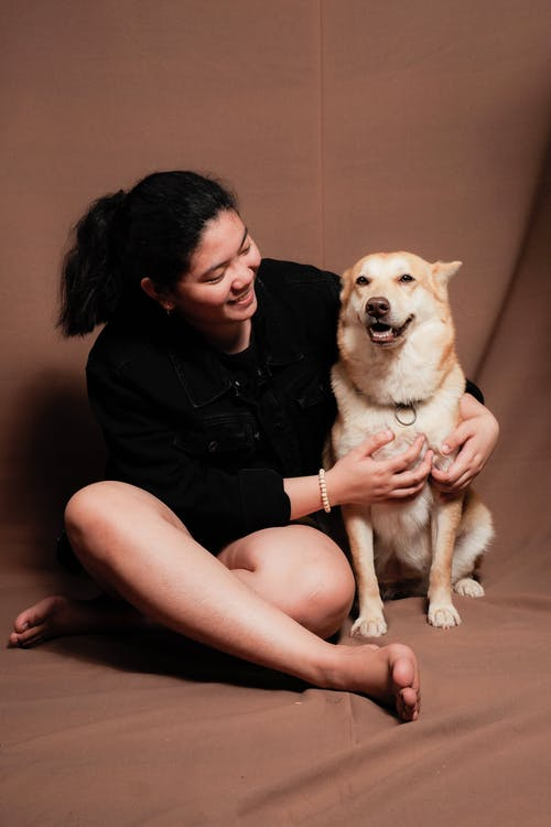 Woman in Black Shirt Sitting on Floor Beside Brown and White Dog