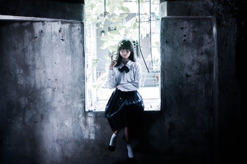 Woman in White and Black School Uniform Sitting on Window