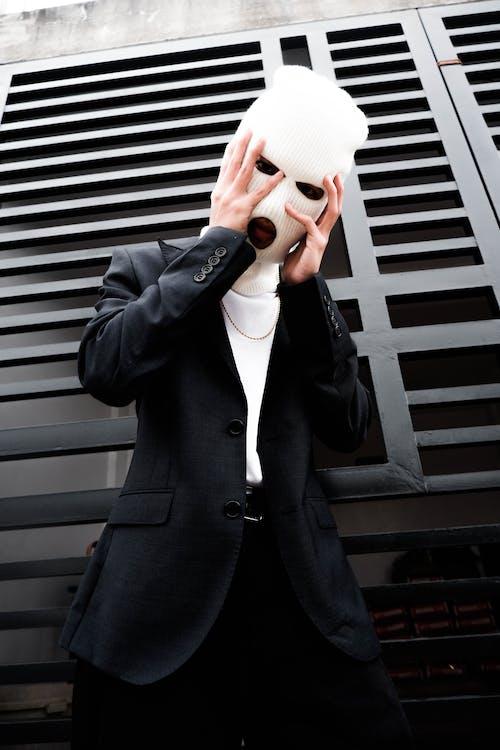 Man in Black Suit Jacket Holding White Face Mask