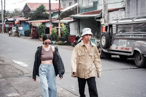 Man in Brown Coat and Blue Denim Jeans Standing on Sidewalk