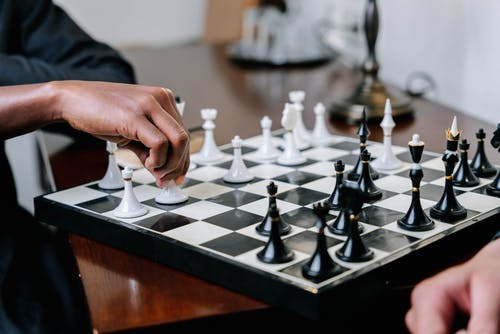 Person Holding White and Black Chess Piece