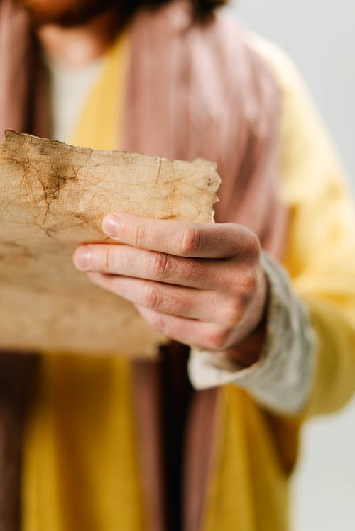 Person in Yellow Robe Holding A Parchment Paper