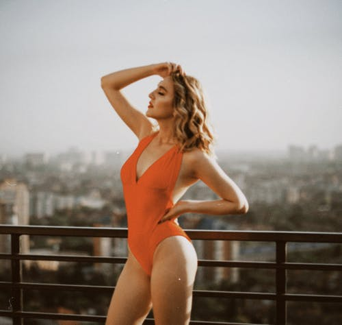 Woman in Orange One Piece Swimsuit Standing on Wooden Fence