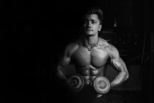 Grayscale Photo of a Man Holding Pair of Dumbbells