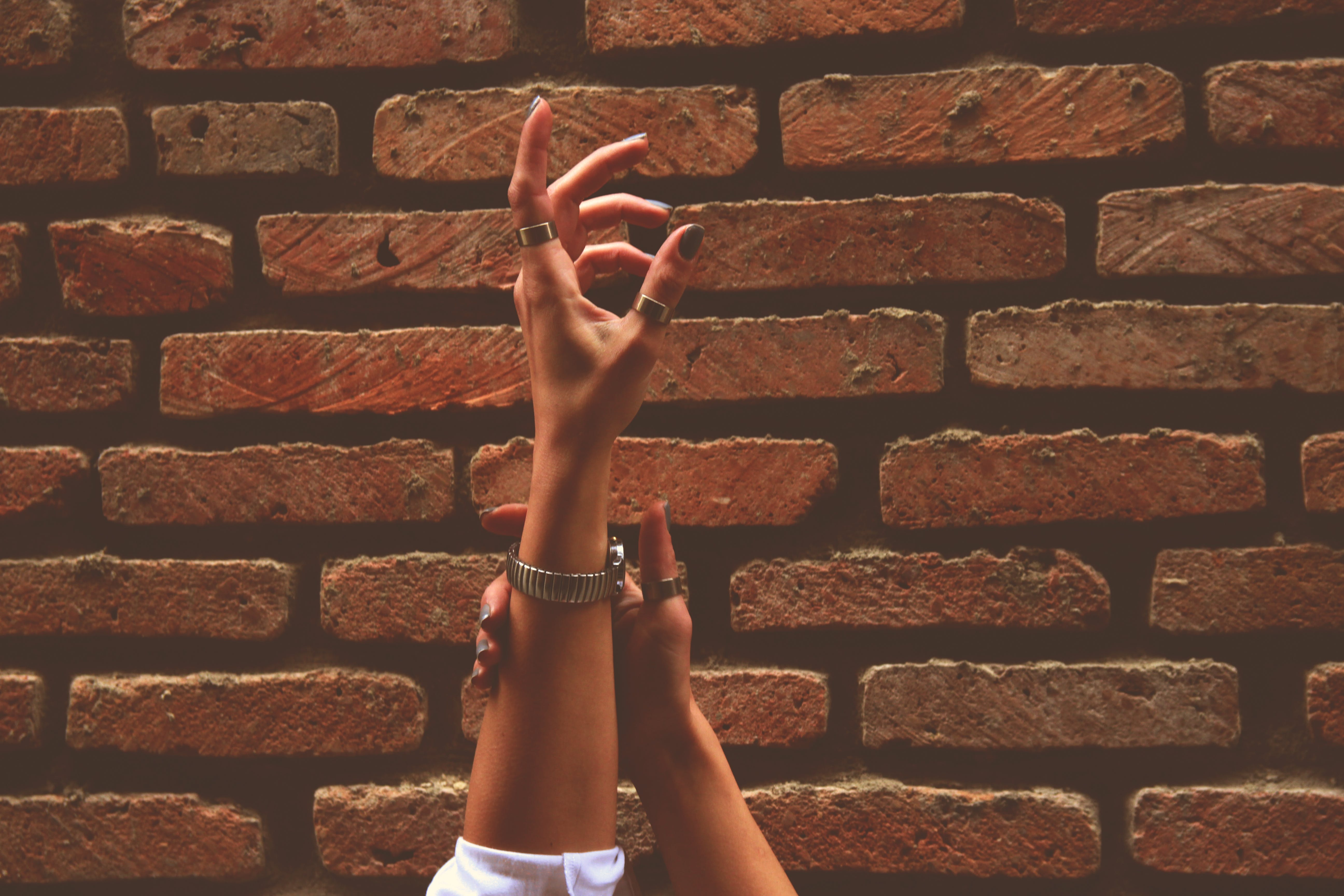 Person Wearing Watch and Rings Raising Left Hand Near Brick Wall