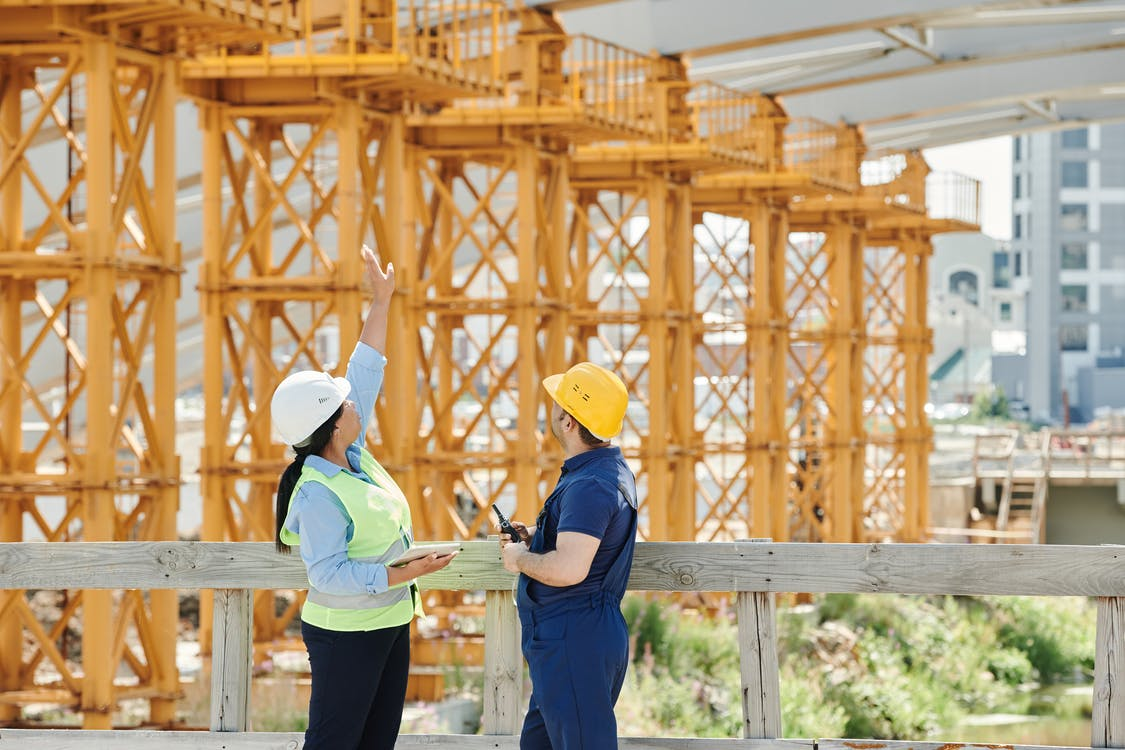Woman in Blue Shirt and Yellow Hat Standing on Wooden Bridge