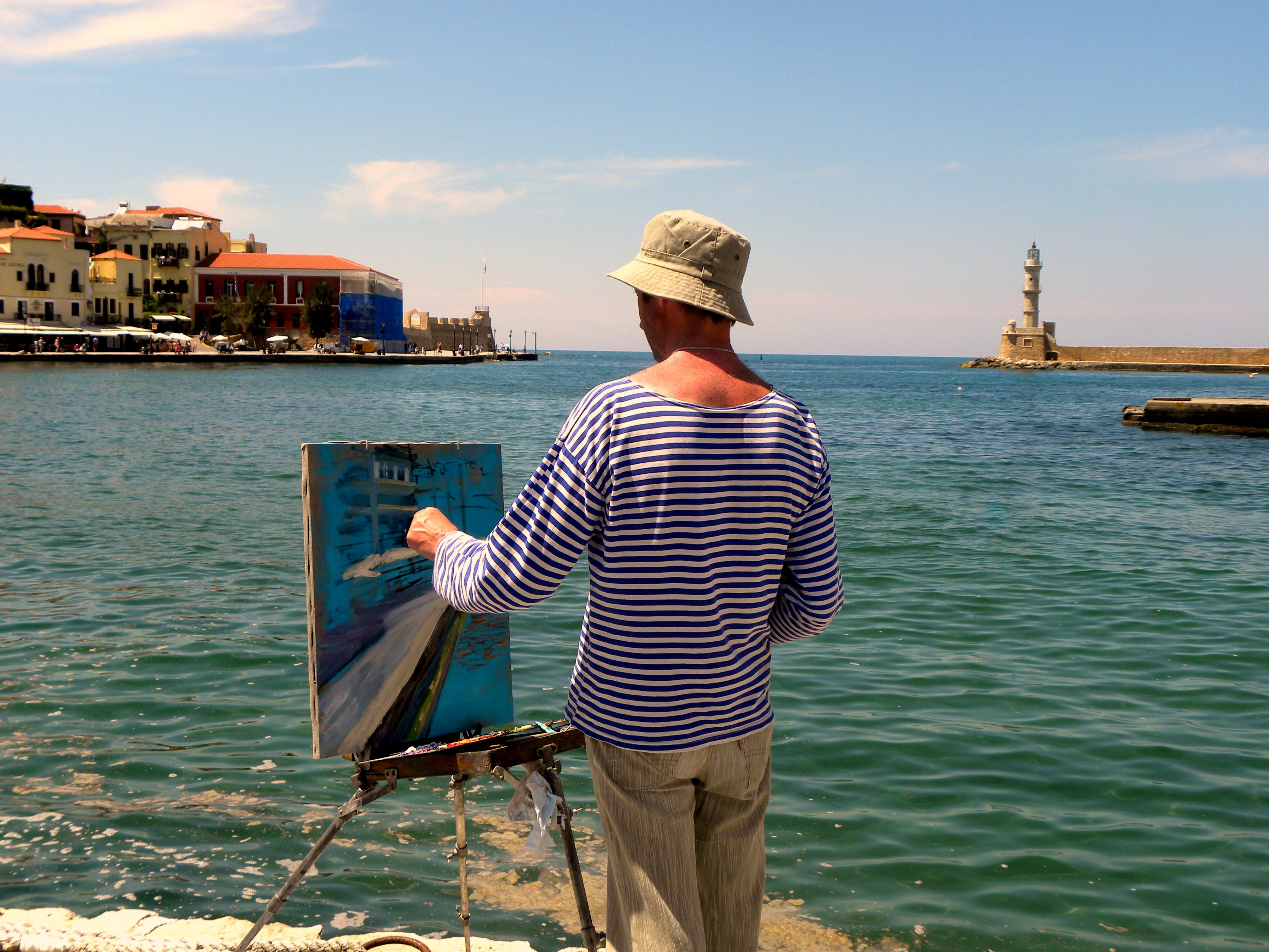 Man in White and Blue Striped Long-sleeved Shirt Painting Near Seashore