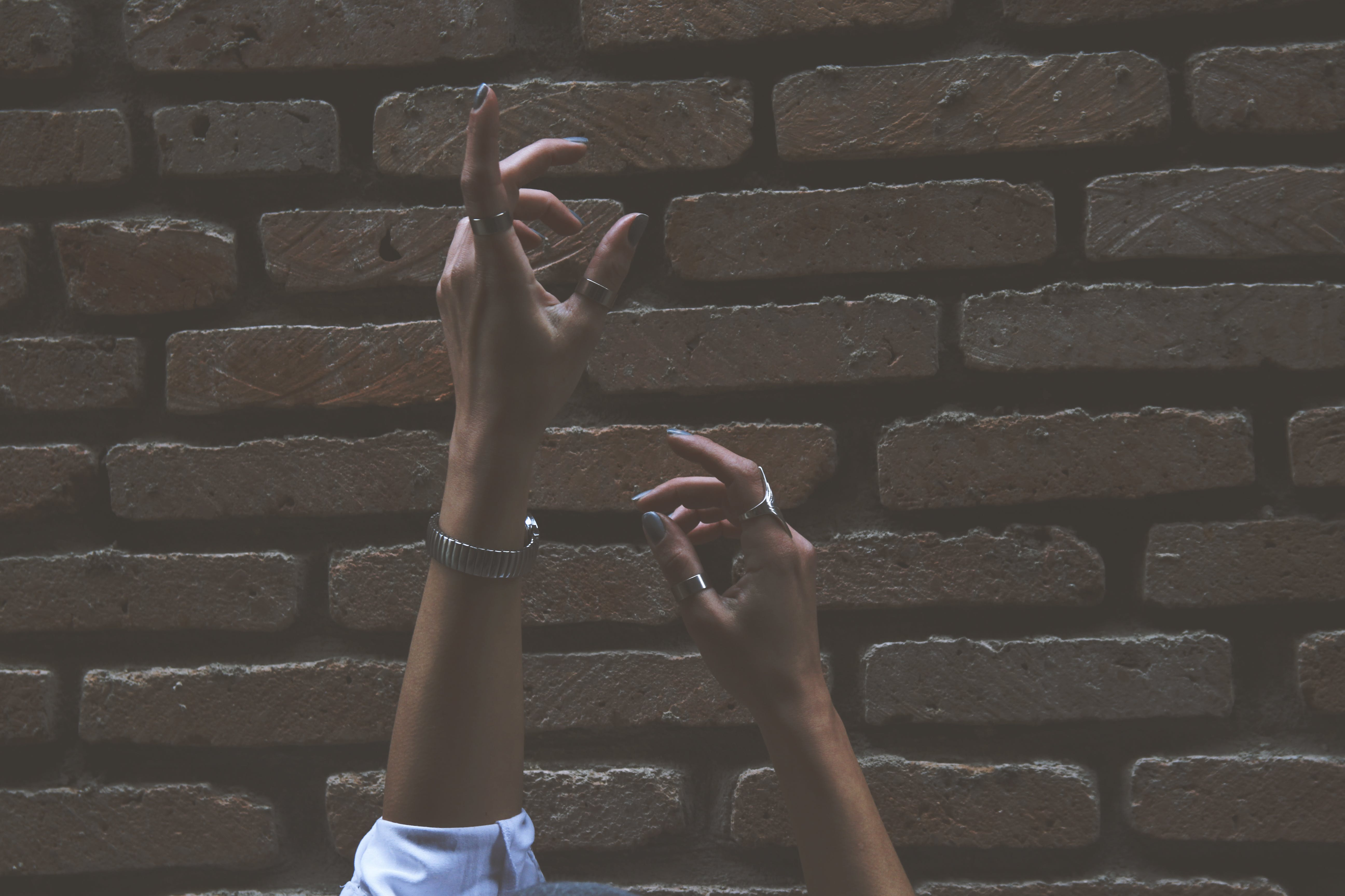 Person Raising Its Two Hand Beside Brown Brick Wall