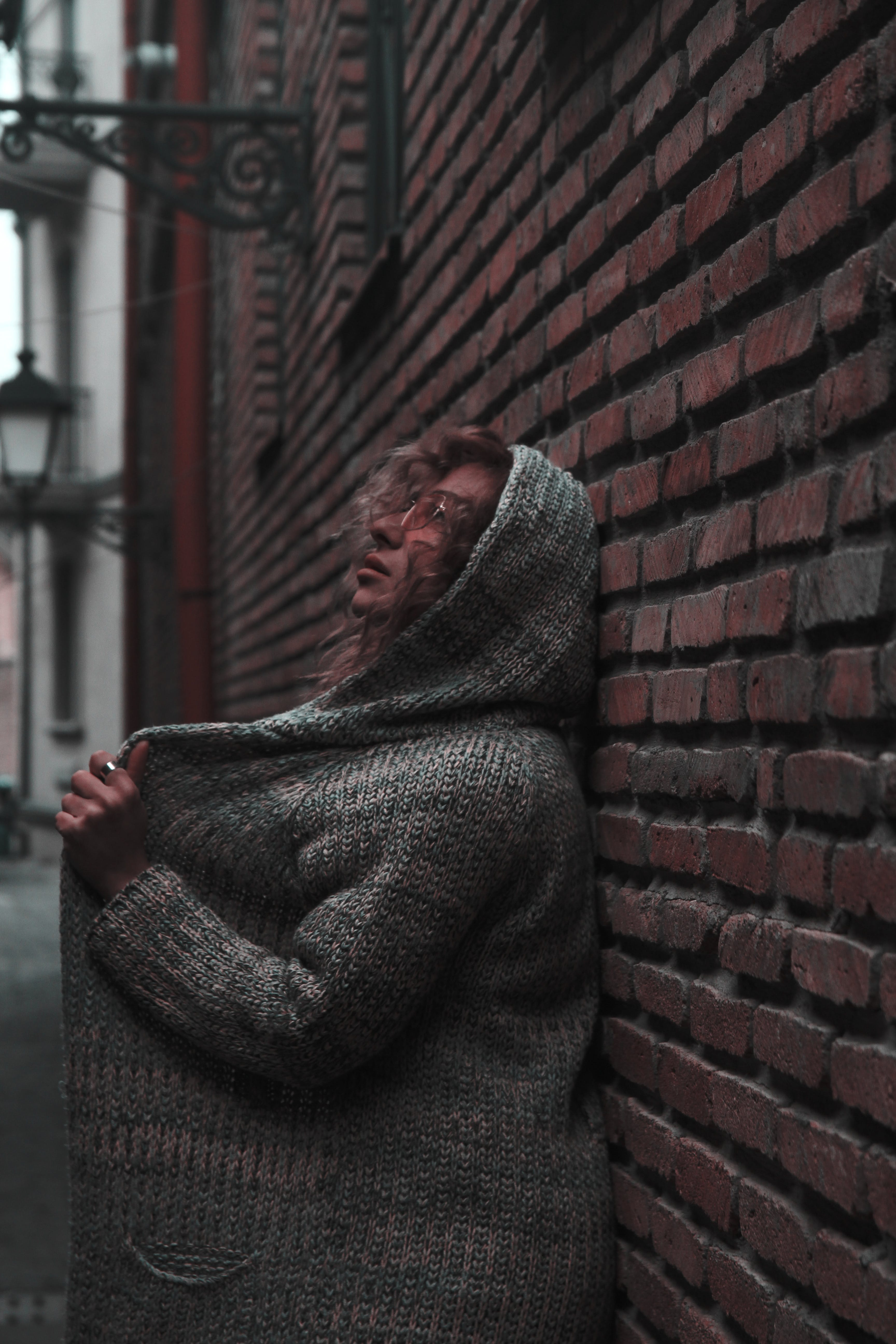Woman in Orange Sunglasses With Space-dye Cardigan With Hoodie Leaning on Wall Brick