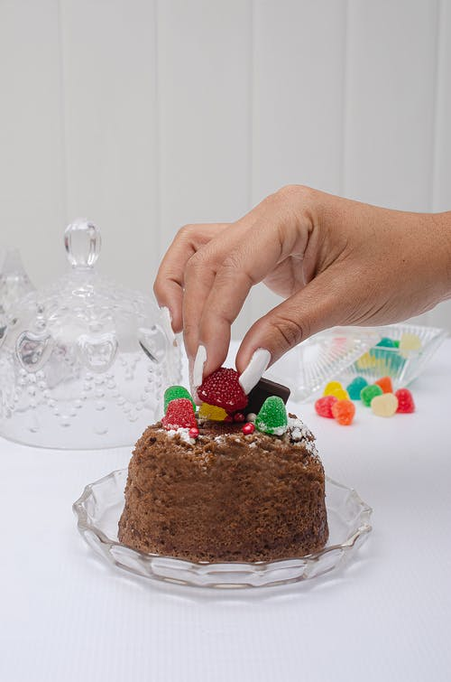 Person Holding Chocolate Cake With Strawberry on Top