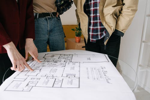 Three People Standing Near Blueprint on Glass Table