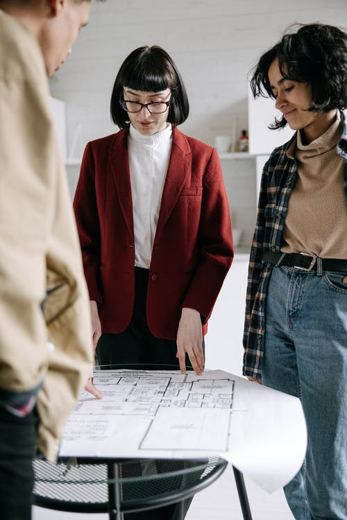 Woman in Red Blazer Looking at Blueprint on Glass Table