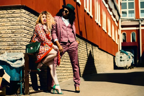 Shallow Focus Photography of Woman in Orange Dress Leaning on Brown Wall Beside Man in Purple Suit Jacket